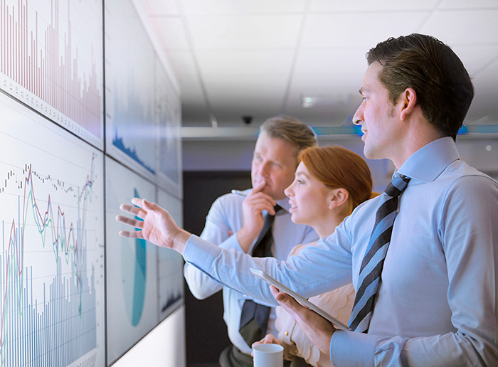 image shows three people looking at charts on a board